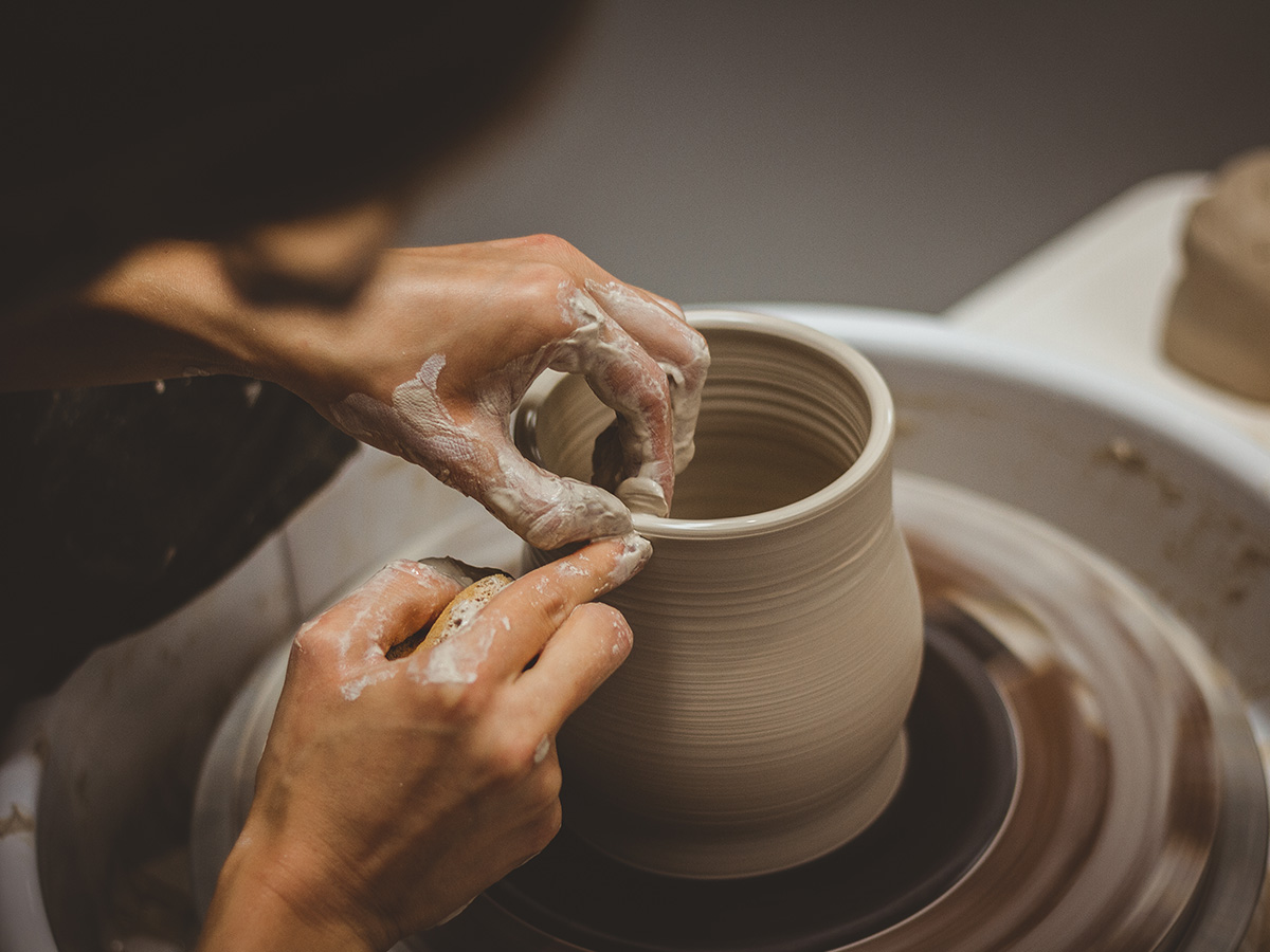 Female potter shaping thrown clay on potters wheel with fingertips at art gallery and ceramic studio